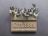 Národní třída, targa commemorativa opera degli artisti Miroslav Krátký e Otakar Příhoda. Le due dita alzate al cielo con il segno di vittoria sono uno dei simboli della Rivoluzione di Velluto.