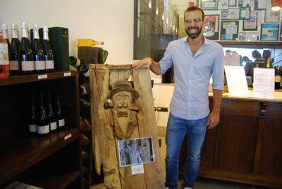 Canelli Luigi Coppo vicino alla scultura lignea del fondatore, Piero Coppo su doghe di botte rovere (ph. Pietro ricciardi © mondointasca.it)