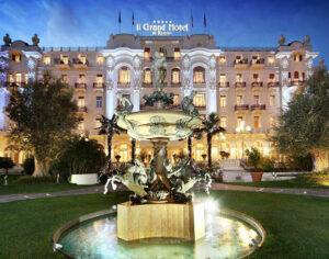 Il Grand Hotel di Rimini di sera. In primo piano la Fontana dei quattro cavalli in  piazza Fellini